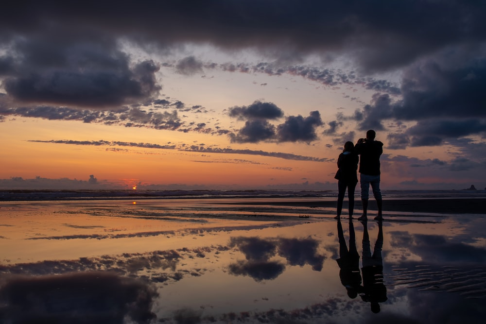 silhouette photography of man and woman standing on seashore during golden hour