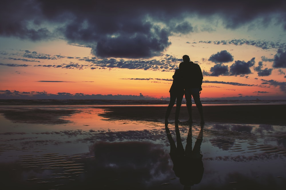 silhouette of two person standing near seashore