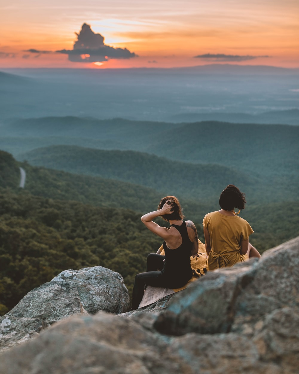 two women sitting on rock formation
