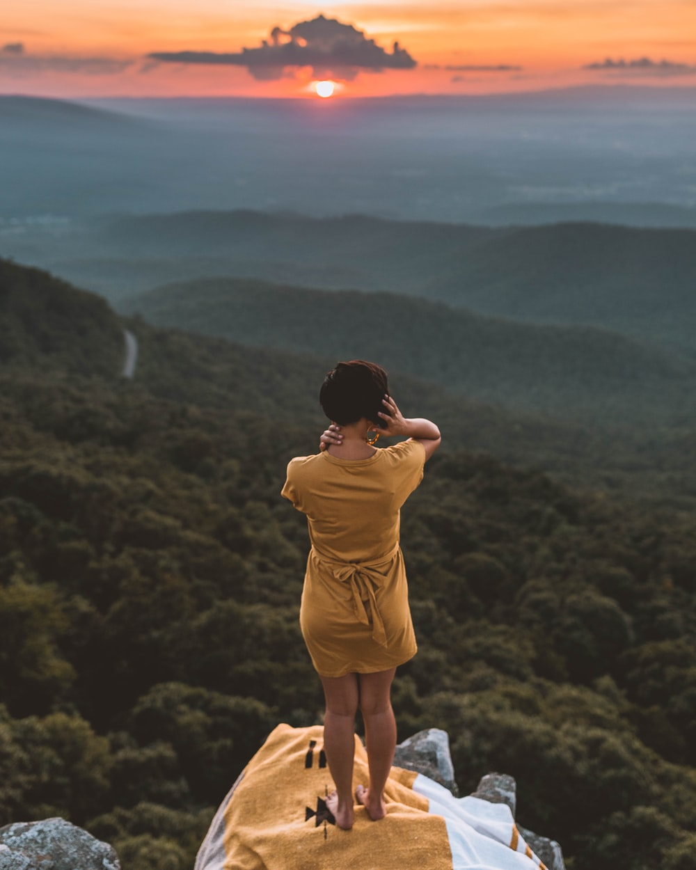 woman in brown dress standing on cliff overlooking forest during golden hour