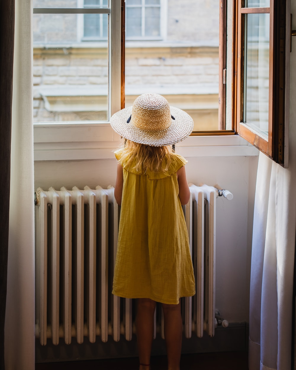 standing girl wearing yellow dress and hat looking outside the window