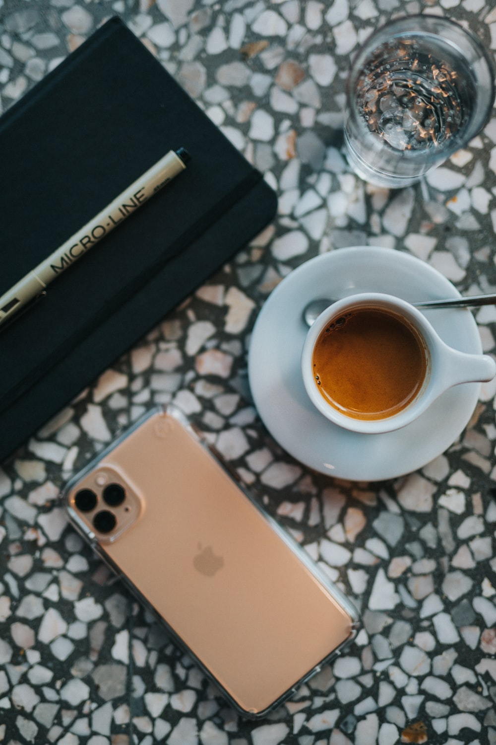 gold iPhone 11 beside cup on table