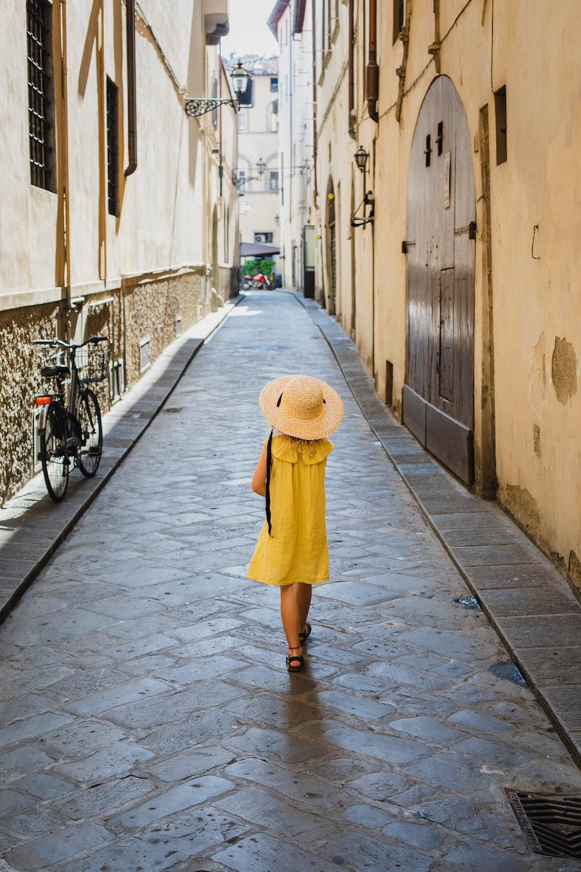 girl walking on pathway during daytime