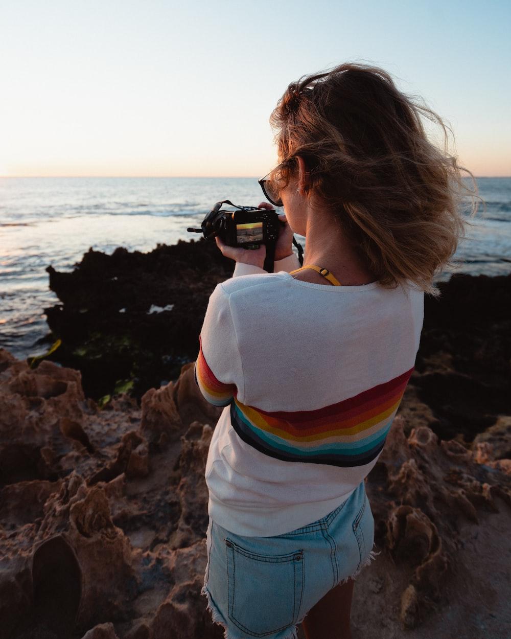 woman taking photo of seashore during daytime
