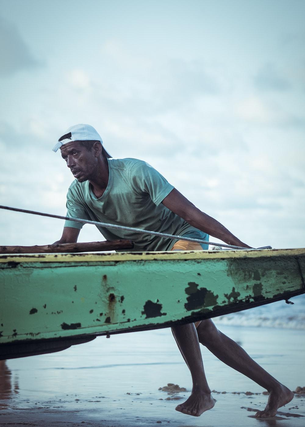 man pushing green boat