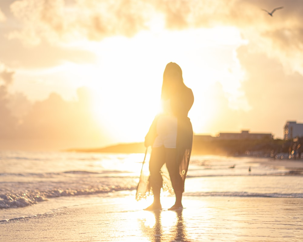 silhouette of woman walking on seashore