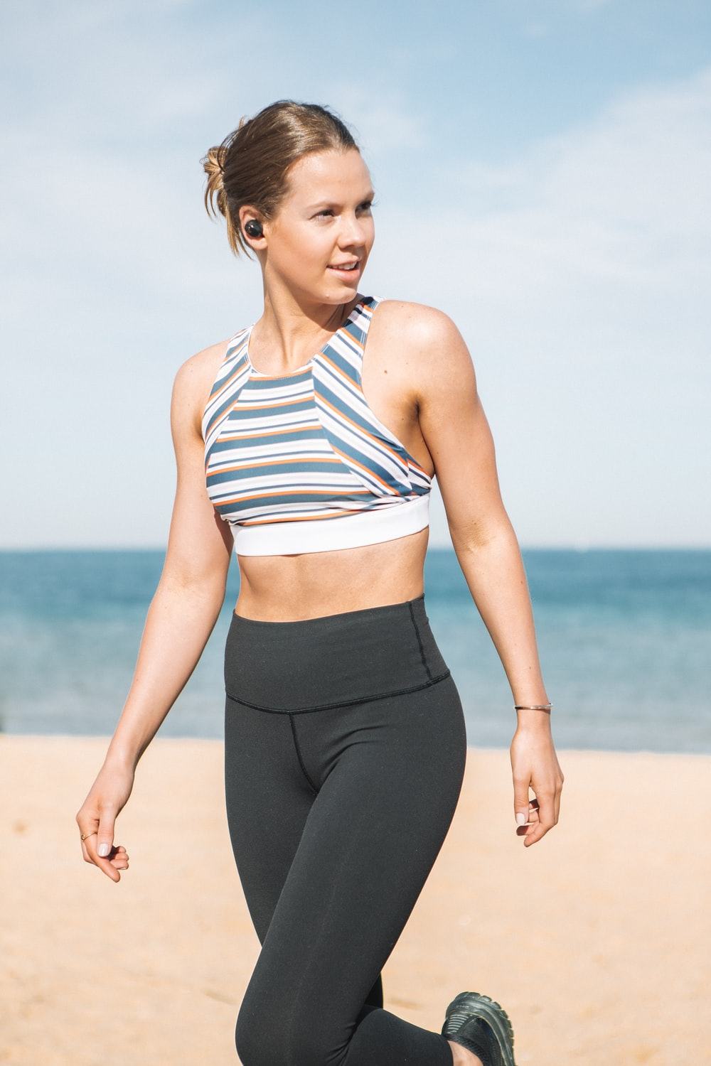 woman wearing sports bra walking on seashore