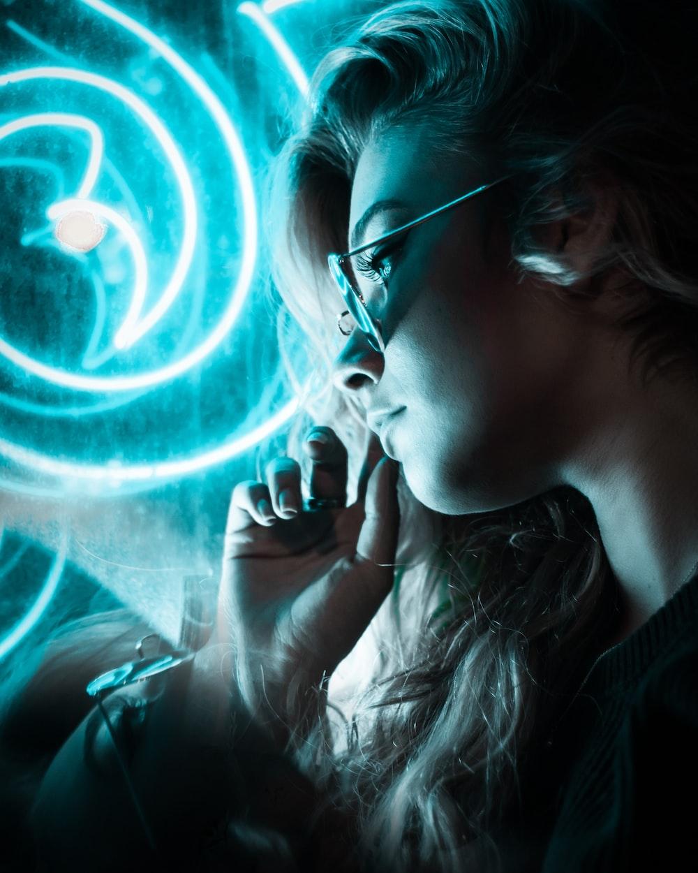 woman wearing sunglasses near blue neon lights