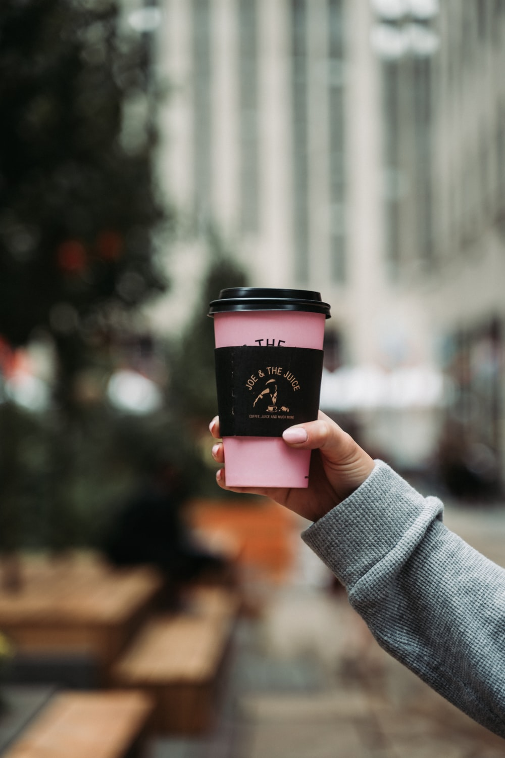 person holding pink and white coffee cup