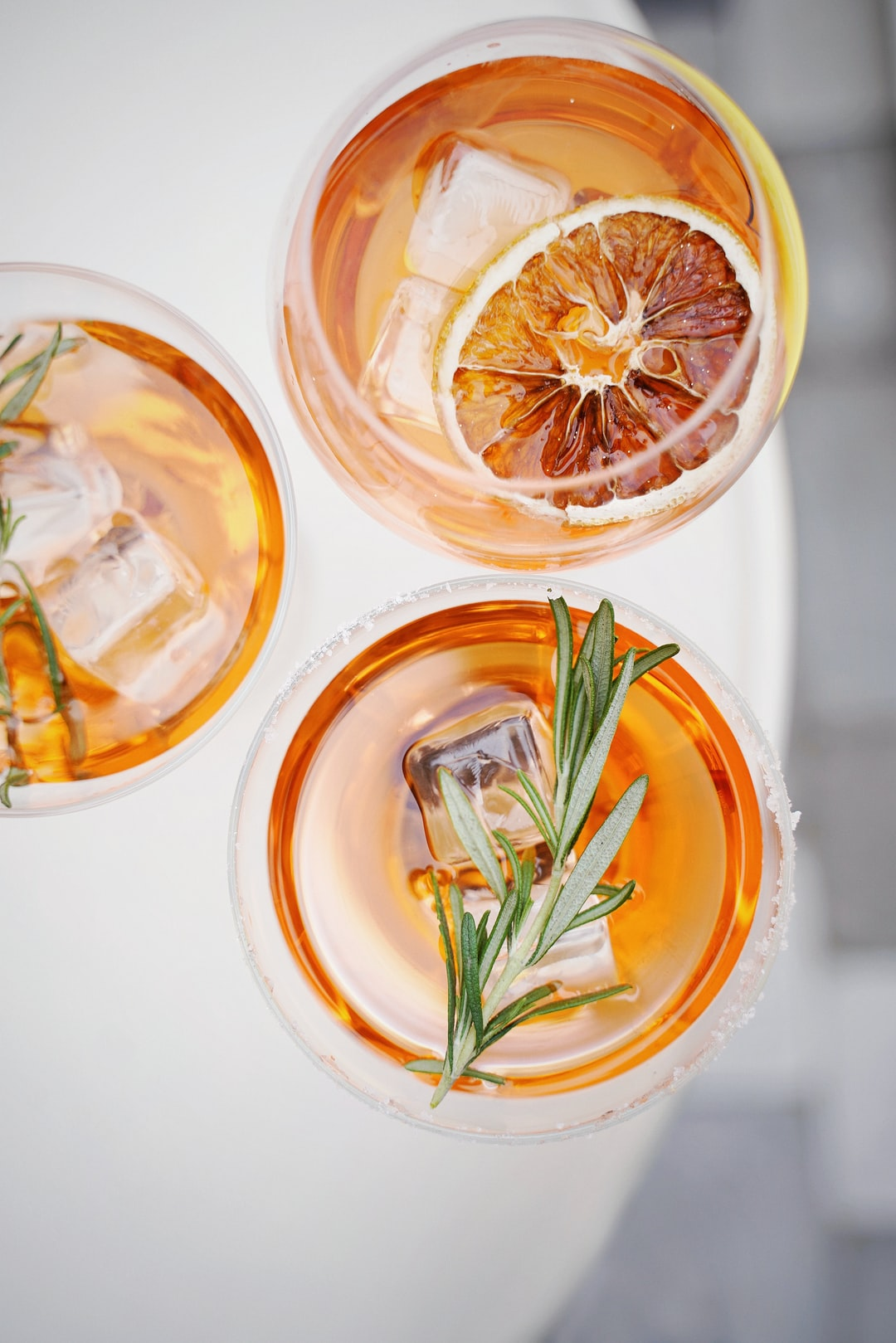 Orange drinks with ice cubes and a sprig of rosemary on top
