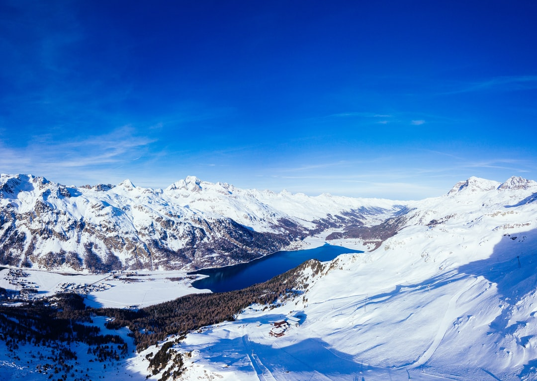 View from mountain down to the towns of Sils, Silvaplana, St. Moritz and Sameden in the swiss alps on a sunny winter day.