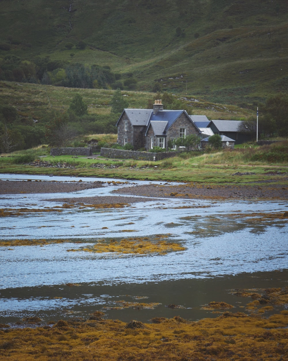 brown and gray concrete house near body of water during daytime