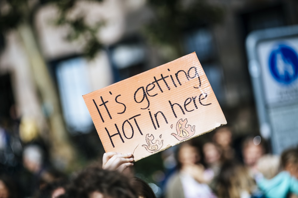 person holding It's getting hot in here signage