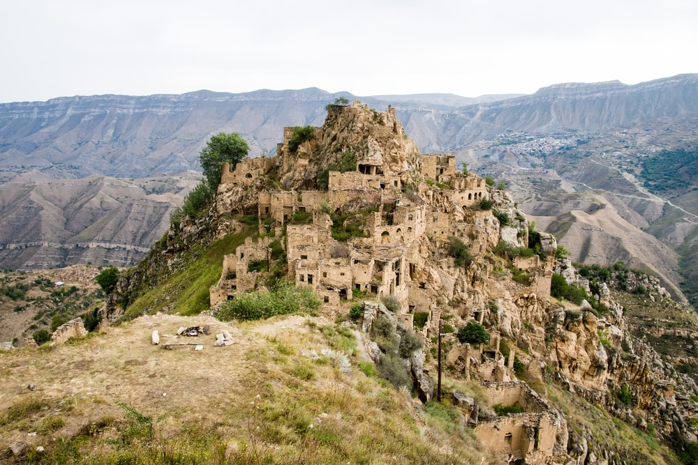 beige wrecked houses on mountain