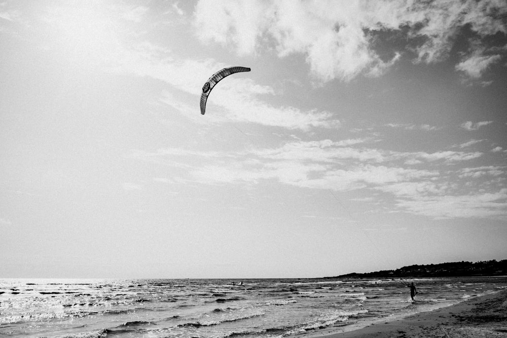 person flying a kite on shore during day