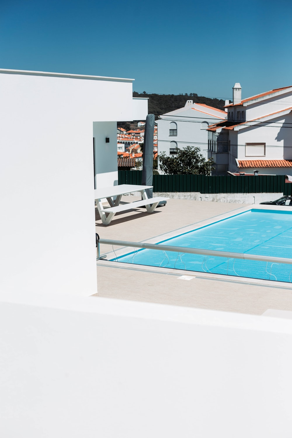 swimming pool beside picnic table during daytime