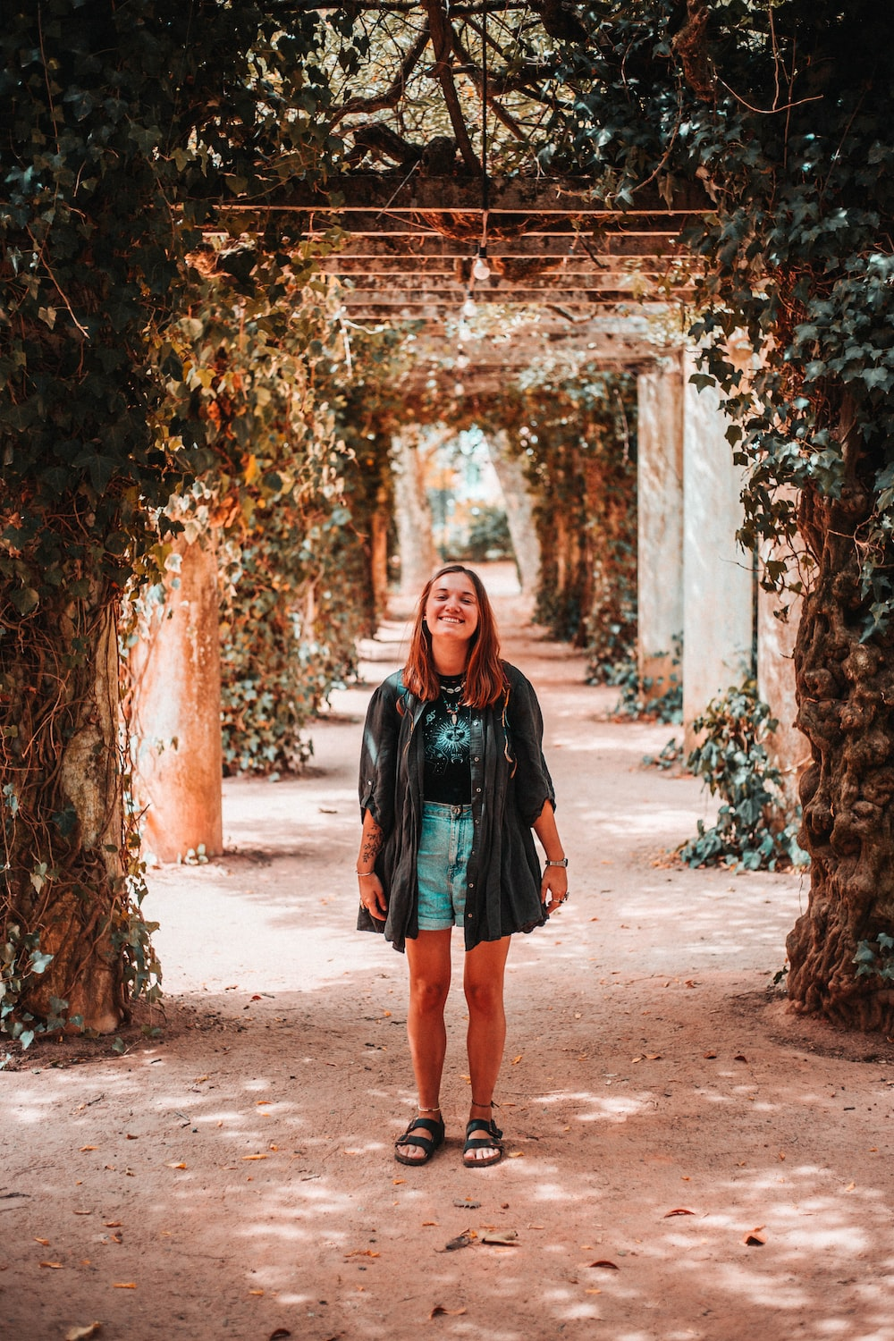 woman standing in tunnel of plants