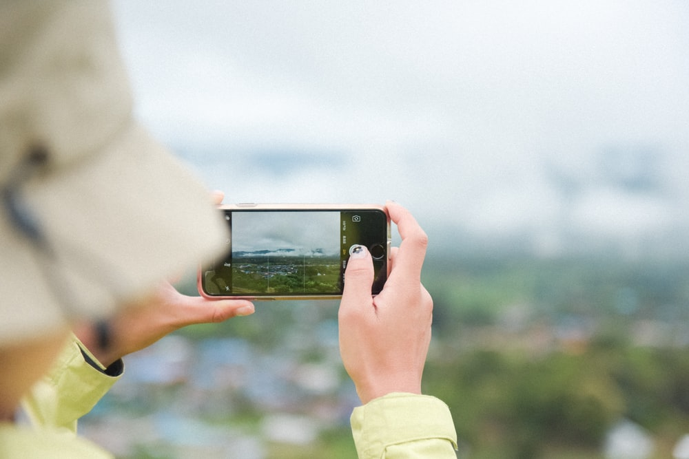 person taking photo of green field