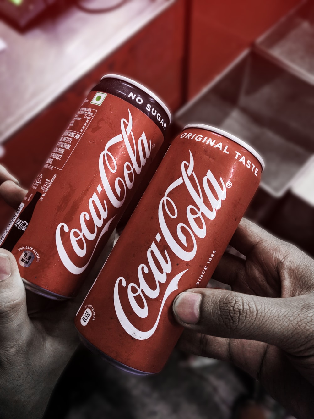 two red-and-white Coca-Cola cans
