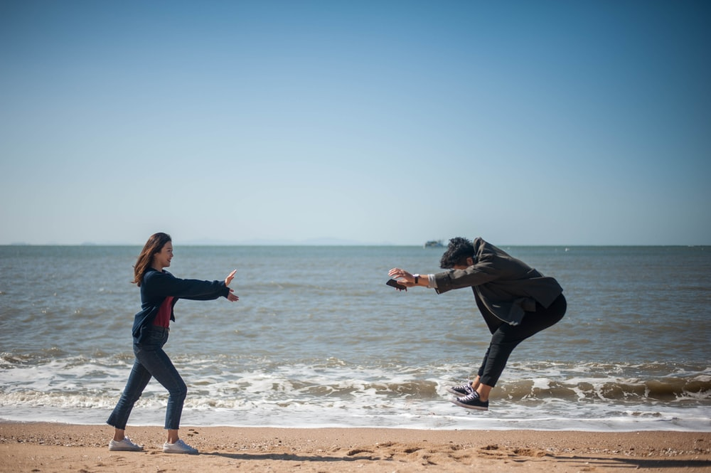 two people playing on seashore during daytime
