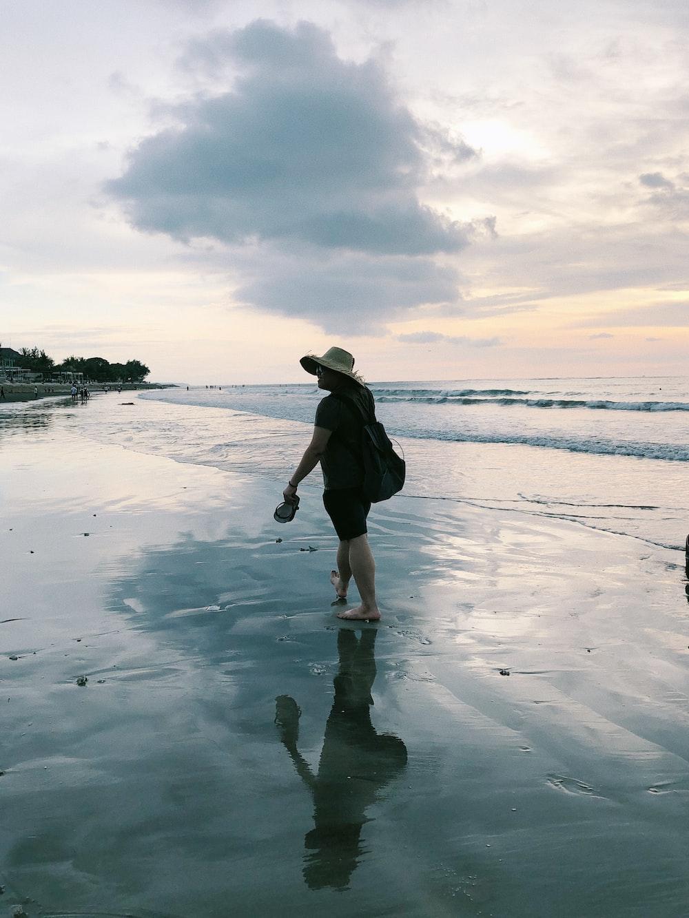 woman in black dress walking on seashore during daytime