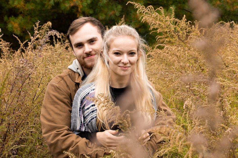 shallow focus photo of man hugging woman