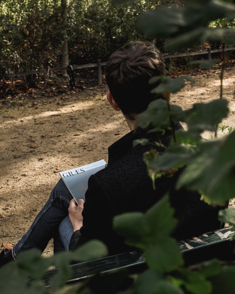 man wearing black long-sleeved shirt sitting on bench
