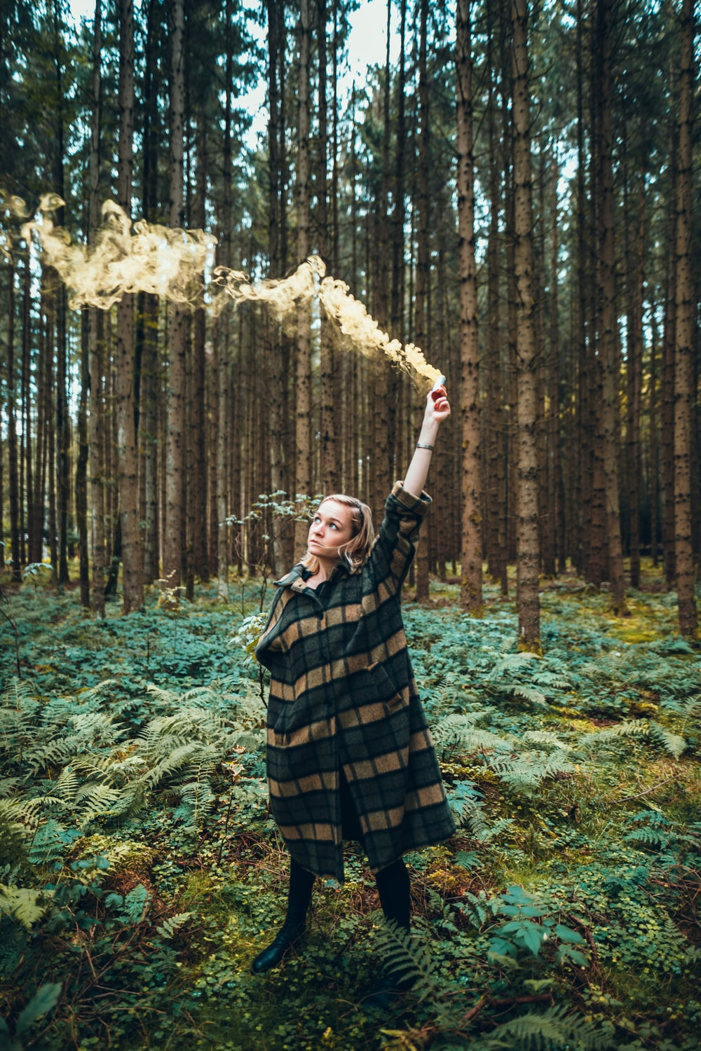 woman in green and brown coat holding flare