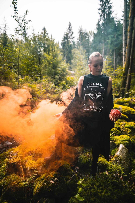 woman wearing black and white Friday-printed shirt beside orange smoke