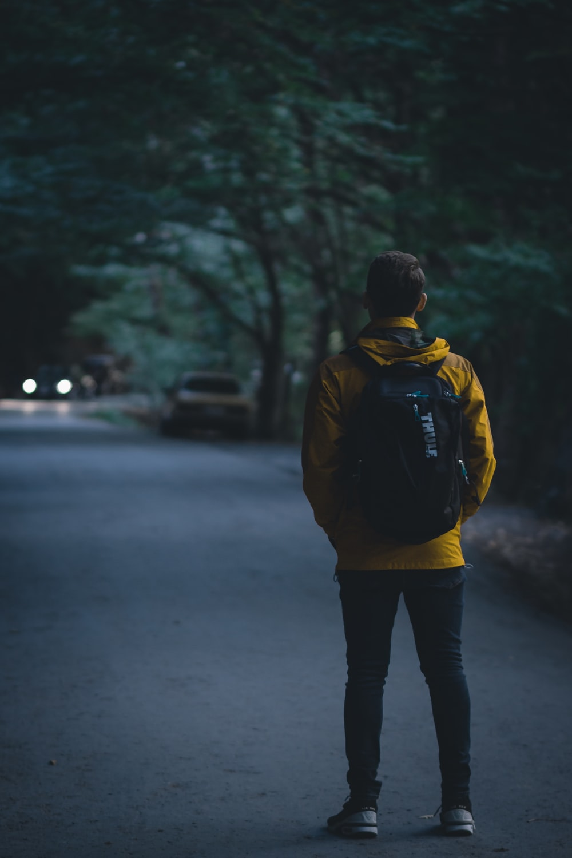 man wearing yellow pullover walking on street