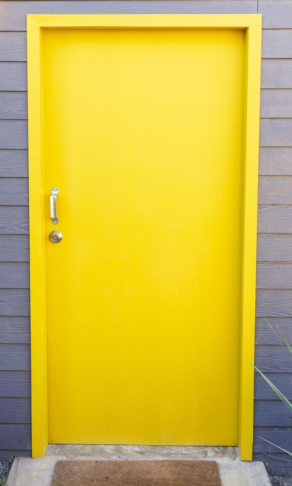 yellow wooden door closed during daytime