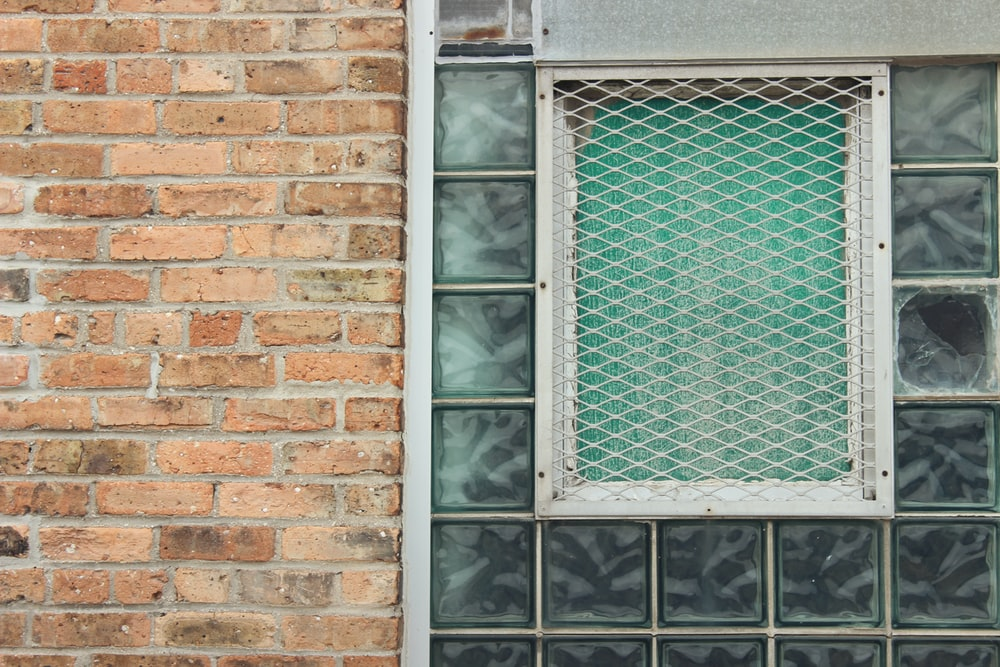 shallow focus photo of window with glass block tiles, exterior view
