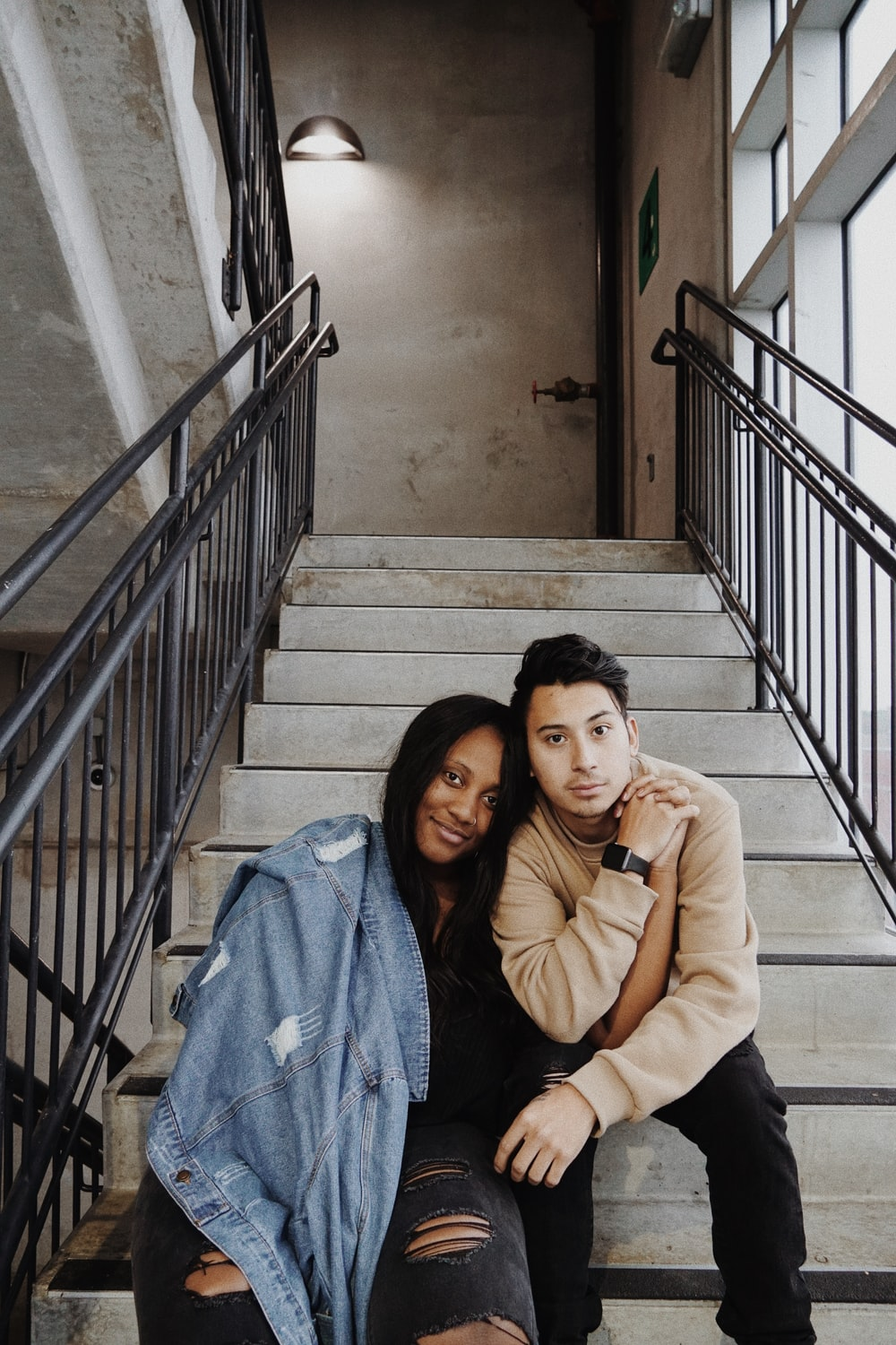 man and woman sitting on concrete steps indoors