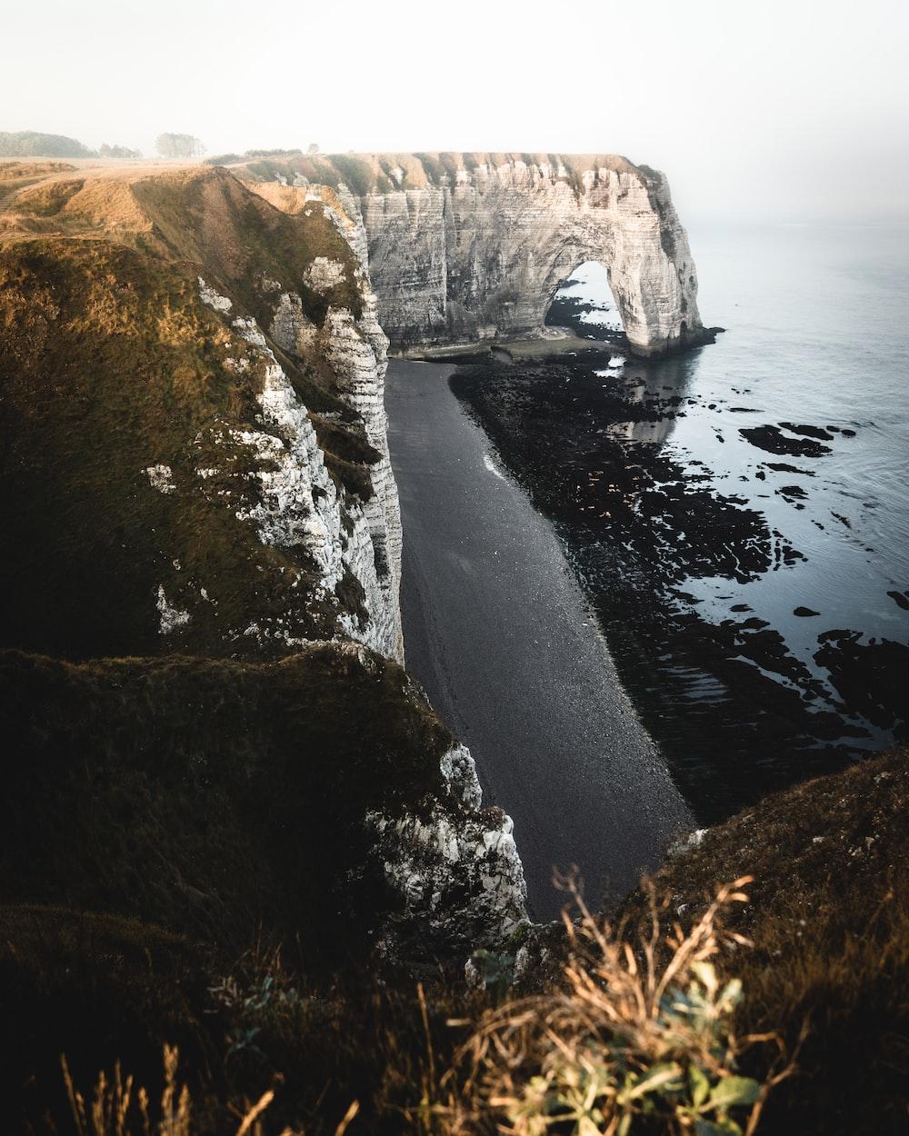 grey cliff beside ocean during daytime