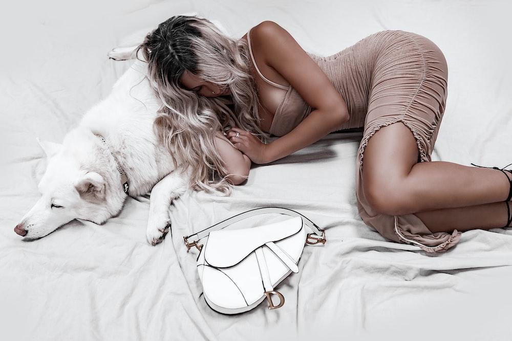 woman lying on white dog