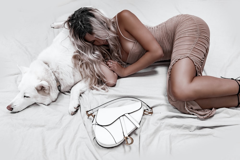 woman lying on white dog