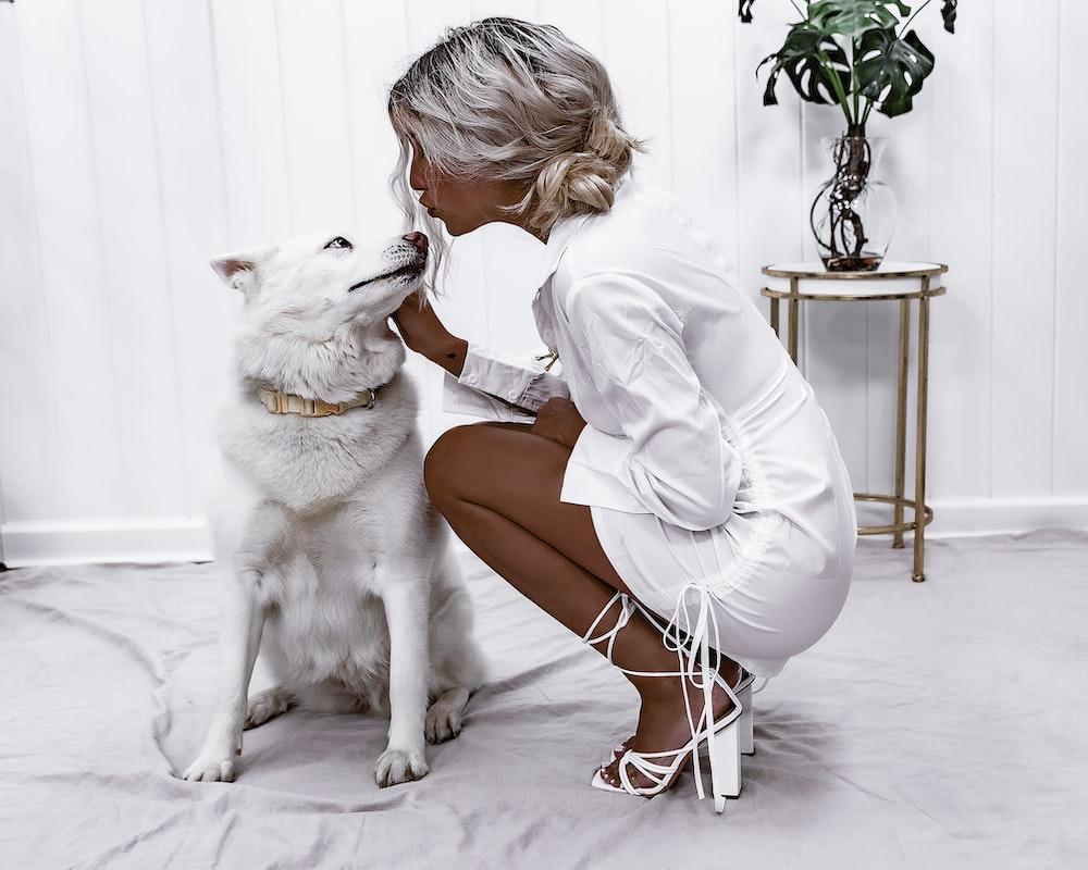 woman beside white dog inside room