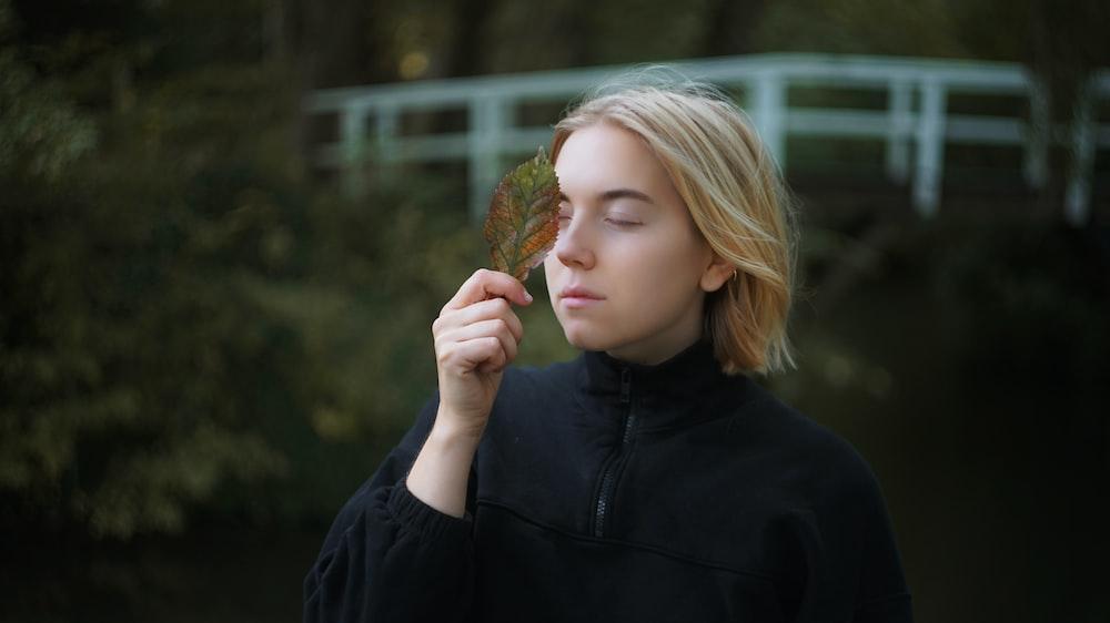 woman wearing black jacket holding brown leaf