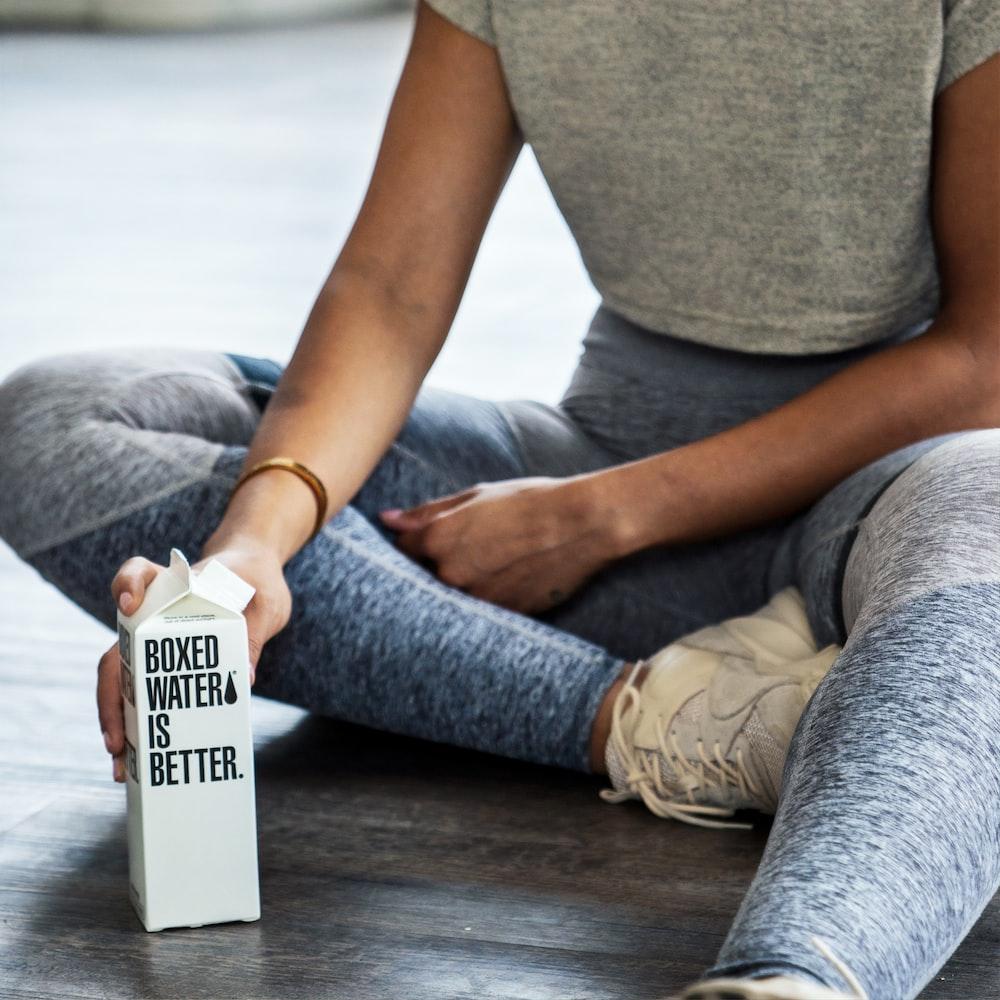 woman sitting on floor holding carton box