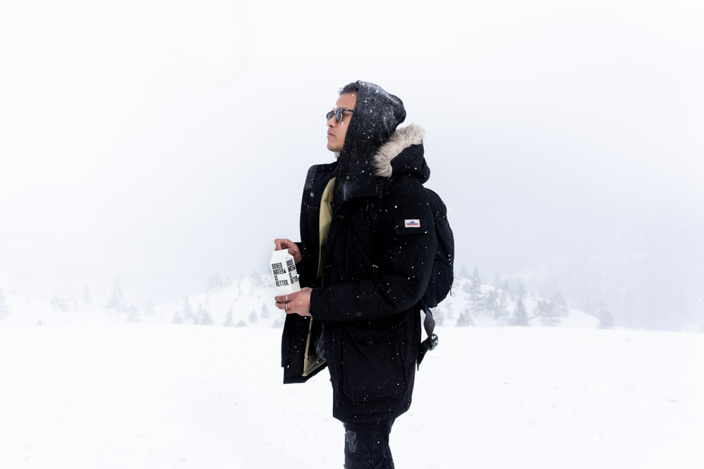 person wearing black hooded jacket holding boxed water while standing on snowy field during daytime