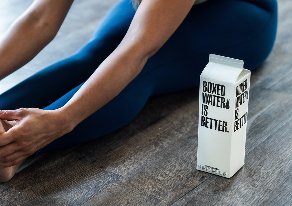person wearing blue leggings sitting near boxed water