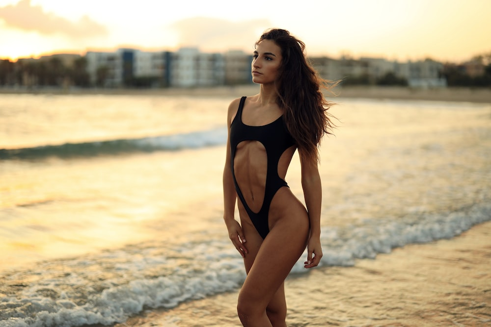 woman wearing black swimsuit on the shore