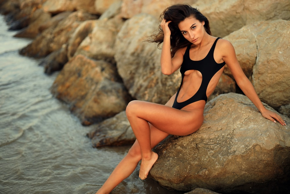 woman in black swimsuit siting on rock