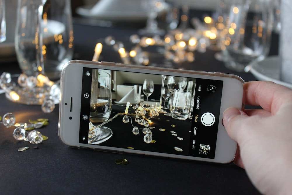 person taking photo of clear footed wine glasses
