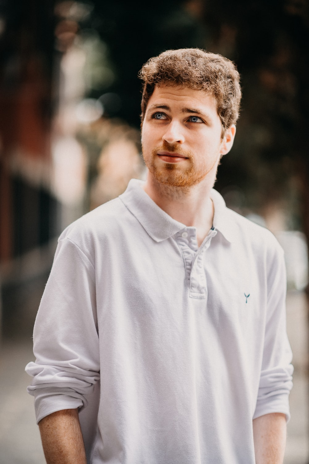 man in white collared long-sleeved shirt standing outdoors
