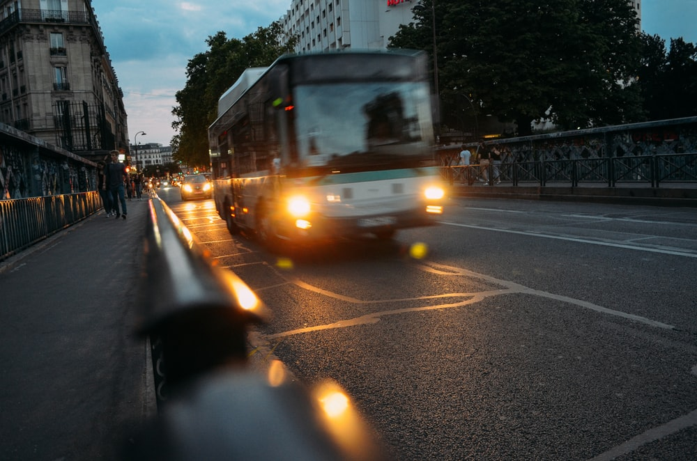 white bus on road at night