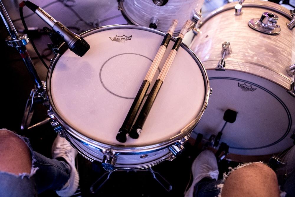pair of drum stick on white snare drum