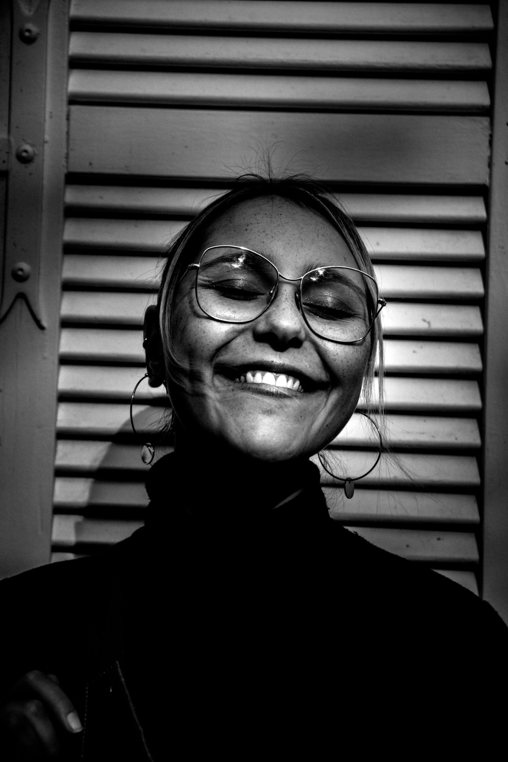 grayscale photography of smiling woman wearing turtle-neck top