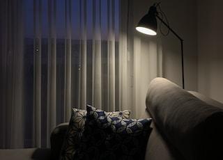 black and white pedestal lamp near white window curtain