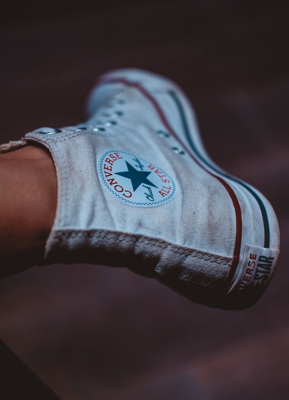 selective focus photography of person wearing white Converse All-Star high-top sneaker